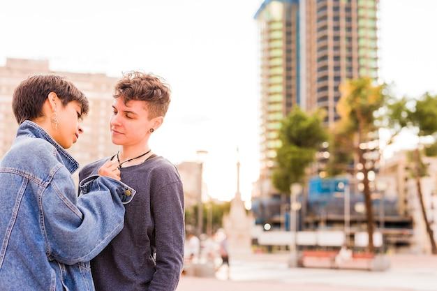 Giovane coppia lesbica maschiaccio androgina transgender non binaria e una donna ispanica con i capelli corti
