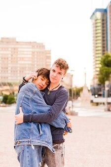 Giovane coppia lesbica maschiaccio transgender non binario e un abbraccio di donna ispanica