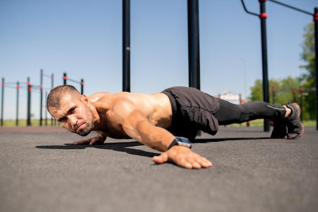 Giovane bodybuilder in topless che allunga il braccio sinistro mantenendo il corpo a terra durante l'esercizio pesante