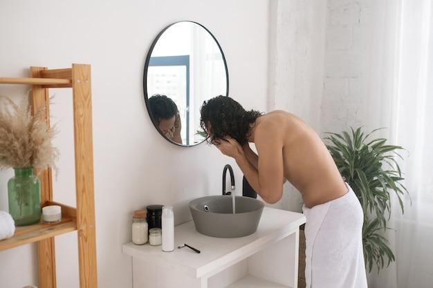 Giovane uomo in topless chinandosi ciotola davanti allo specchio mentre si lava la faccia la mattina in bagno