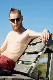 Giovane uomo in topless con barba lunga e occhiali da sole che riposa sulla panchina all'aperto, prendere il sole e godersi il pomeriggio estivo