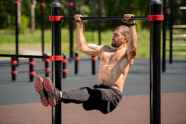 Giovane atleta muscoloso in topless che appende sulla barra dello sport mentre si tira su sul campo sportivo durante l'allenamento