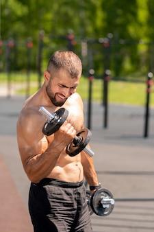 Giovane uomo muscoloso in topless in pantaloncini neri che si esercita con manubri pesanti all'aperto mattina di sole