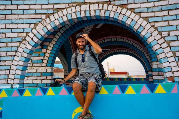 Un giovane turista su una bellissima terrazza di una tradizionale casa blu in un villaggio nubiano vicino al fiume nilo e vicino alla città di assuan. egitto