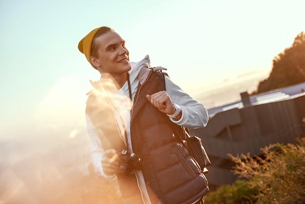Il giovane blogger turistico in cappello fa una foto dell'alba