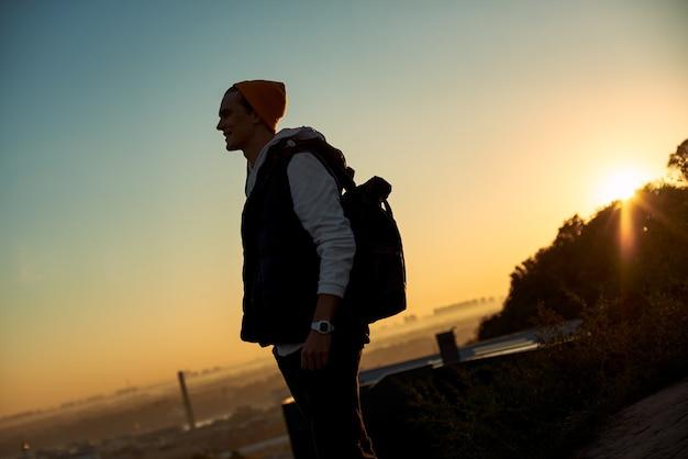 Il giovane blogger turistico in cappello incontra il tramonto