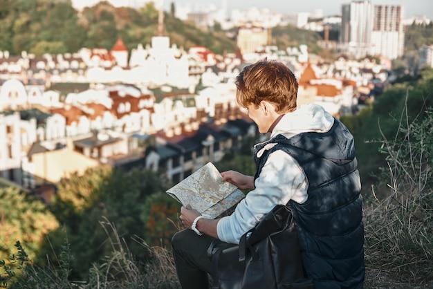 Il giovane blogger turistico sta esplorando la vista posteriore della mappa