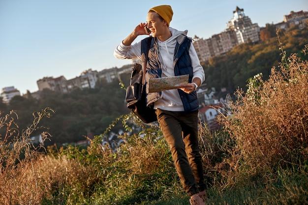 Il giovane blogger turistico sta esplorando la mappa e parlando allo smartphone