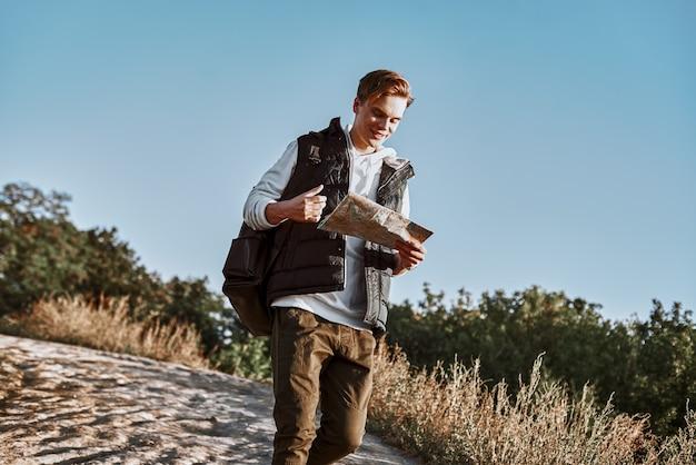 Il giovane blogger turistico sta esplorando la mappa