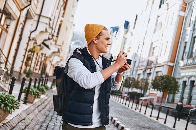 Il giovane blogger turistico sta camminando con la macchina fotografica nella vecchia città