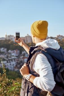 Il giovane blogger turistico sta facendo la retrovisione del selfie