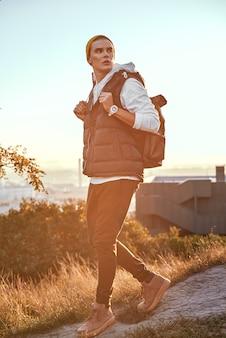 Il giovane blogger turistico in cappello arancione cammina a sfondi è l'alba
