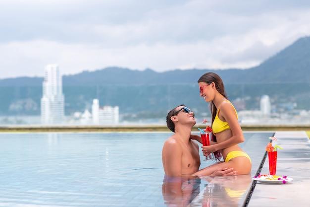 Giovani coppie turistiche sullo stagno di infinito che bevono i cocktail al ricorso sulla spiaggia