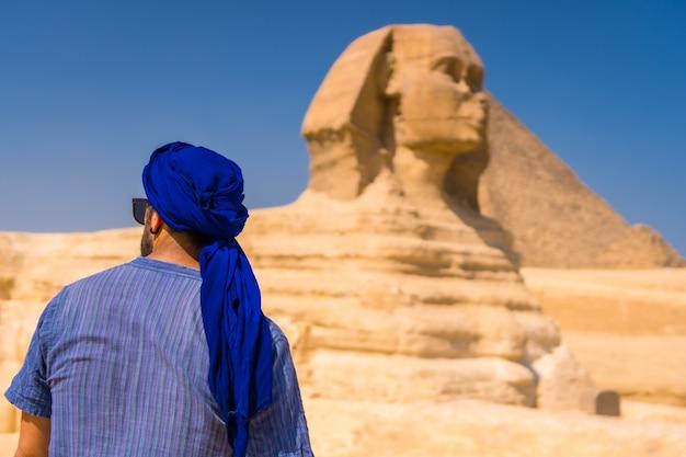Un giovane turista che si gode e ammira la grande sfinge di giza vestito di blu e di un turbante blu. cairo, egitto