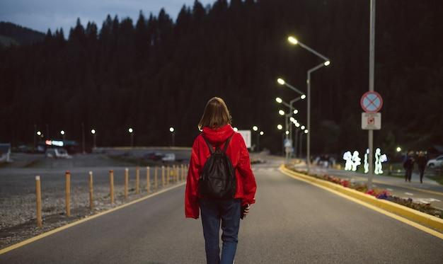 Vista posteriore della giovane ragazza turistica sulla strada che va alla foresta di montagna nelle luci della strada