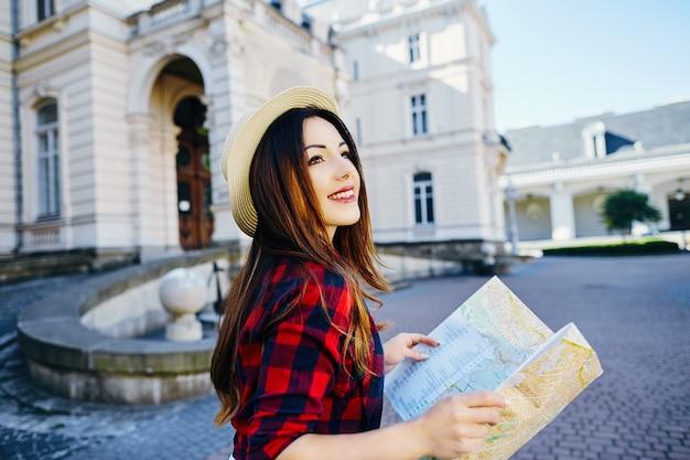 Giovane ragazza turistica con capelli castani che indossa un cappello e camicia rossa, tenendo la mappa al vecchio sfondo della città europea e sorridente, viaggiando