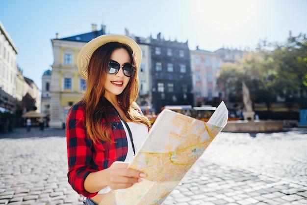Giovane ragazza turistica con capelli castani che indossa cappello, occhiali da sole e camicia rossa, che tiene la mappa al vecchio fondo della città europea e sorridente, in viaggio, ritratto