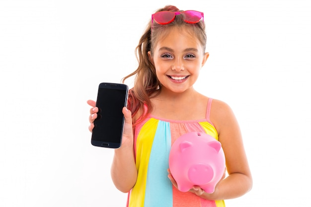 Ragazza giovane turista con un telefono con un modello rosa salvadanaio su un muro bianco