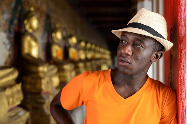 Giovane uomo turistico che pensa contro la vista delle strutture allineate di buddha in tempio di wat arun