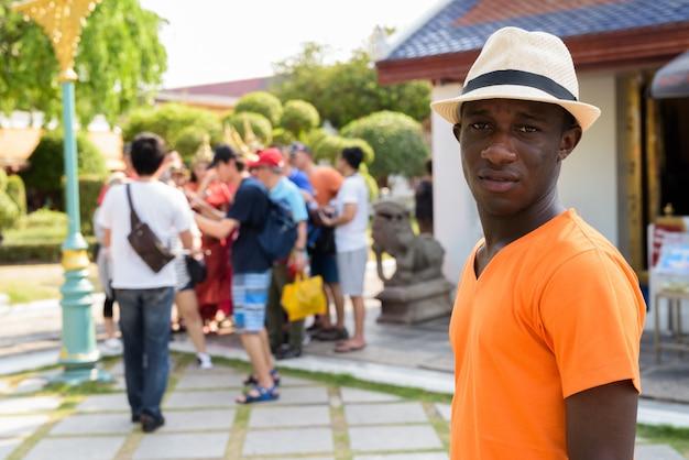 Uomo giovane turista con un gruppo di turisti asiatici a scattare foto con donne tailandesi che indossano abiti tradizionali a bangkok in thailandia al tempio di wat arun