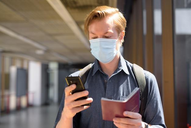 Uomo giovane turista con maschera utilizzando il telefono durante il controllo del passaporto in aeroporto