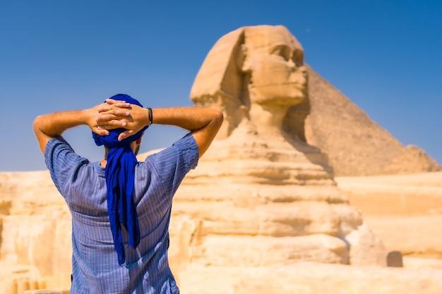 Un giovane turista vicino alla grande sfinge di giza vestito di blu e di un turbante blu, da dove partono le miramidi di giza. cairo, egitto