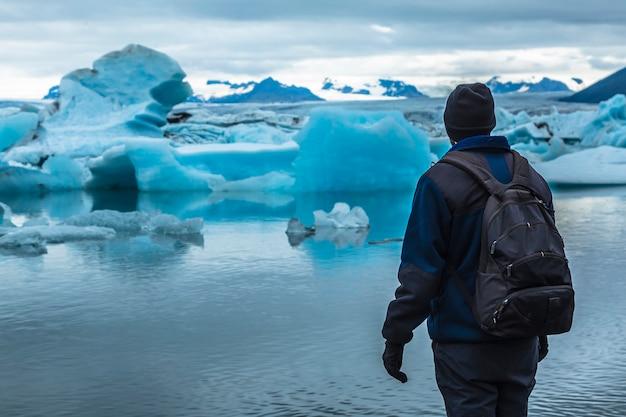 Un giovane turista con zaino sul lago ghiacciato di jökulsárlón ad agosto. islanda