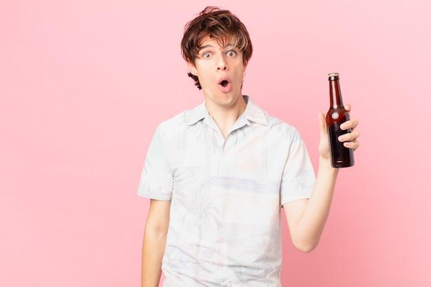 Giovane turista con una birra che sembra molto scioccato o sorpreso
