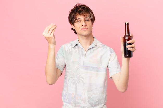 Giovane turista con una birra che fa capice o un gesto di denaro che ti dice di pagare