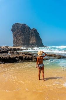 Un giovane turista con un cappello nel roque del moro della spiaggia di cofete del parco naturale di jandia, barlovento, a sud di fuerteventura, isole canarie. spagna