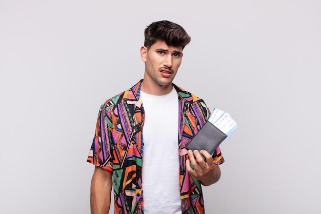 Giovane turista con un passaporto che si sente perplesso e confuso, con un'espressione stupita e sbalordita guardando qualcosa di inaspettato