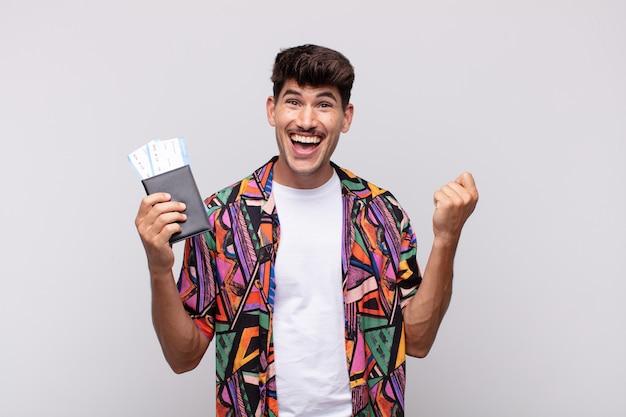 Giovane turista con un passaporto che si sente scioccato, eccitato e felice, ridendo e festeggiando il successo, dicendo wow!