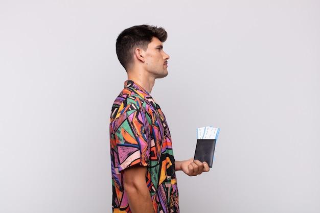 Giovane turista con un passaporto in vista di profilo che cerca di copiare lo spazio davanti, pensare, immaginare o sognare ad occhi aperti
