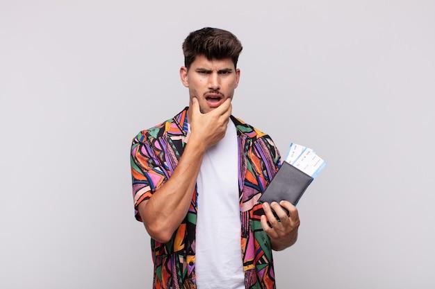 Giovane turista con un passaporto con la bocca e gli occhi spalancati e la mano sul mento, che si sente spiacevolmente scioccato, dice cosa o wow