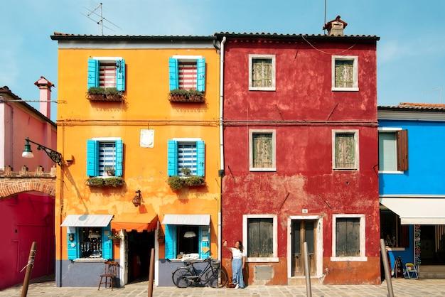 Una giovane donna turistica per le strade colorate di burano a venezia mentre sorride e visita la città italiana