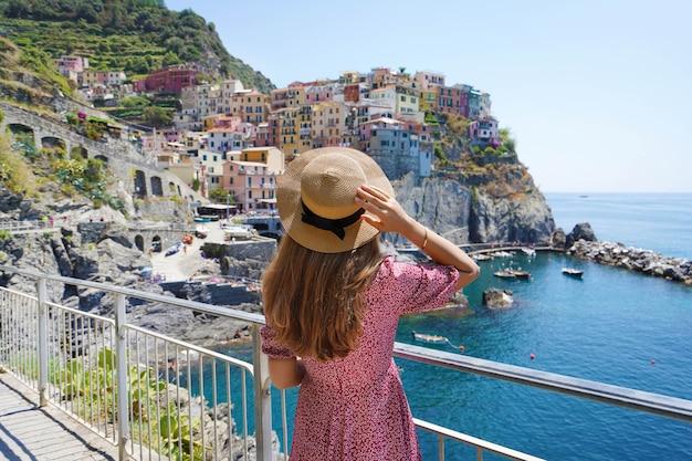 Giovane donna turistica che si diverte a viaggiare in italia. bella ragazza alla moda con cappello e vestito guardando il villaggio di manarola a strapiombo sul mare, cinque terre, italia.