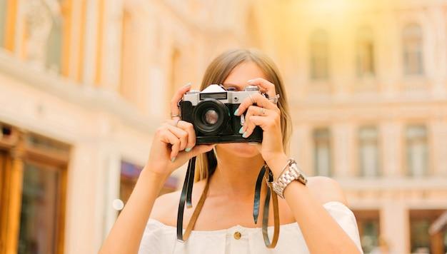 Giovane donna turistica in abiti alla moda con fotocamera retrò