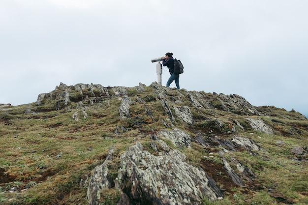 Giovane donna turistica guardando attraverso un binocolo ad alta potenza a gettoni sulle montagne del caucaso, kazbegi, georgia
