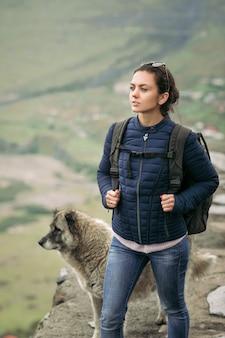Giovane donna turistica con uno zaino sullo sfondo delle montagne del caucaso, in georgia in una giornata nebbiosa