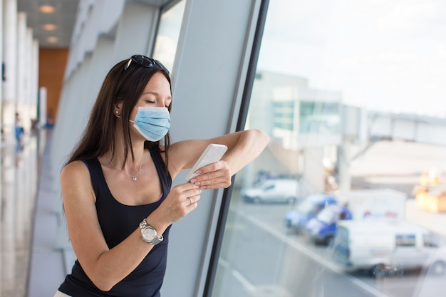 Giovane donna turistica con bagaglio in aeroporto internazionale