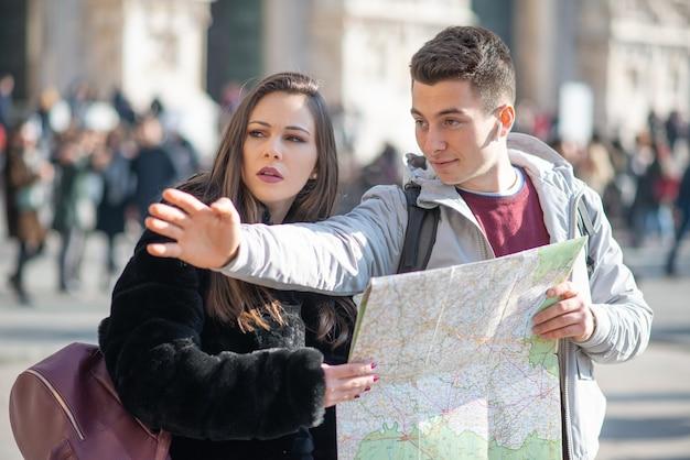 Coppia di giovani turisti in possesso di una mappa a milano, italia