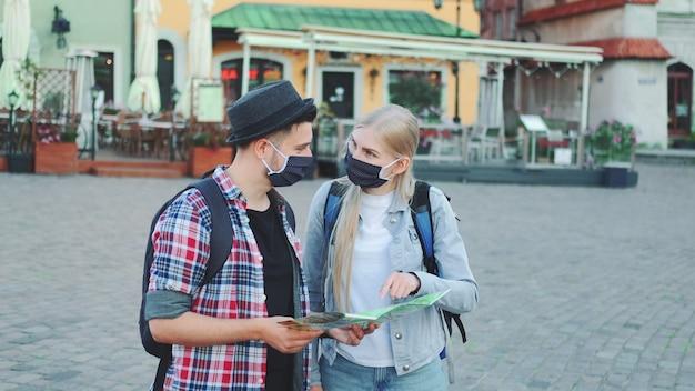 I giovani turisti si accoppiano in maschere protettive controllando la mappa sulla piazza centrale della città, quindi ammirando un posto bellissimo. viaggia durante la pandemia.