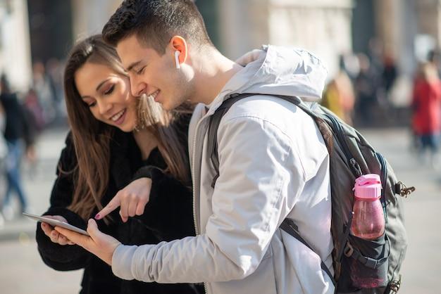 Coppia di giovani turisti che utilizza una tavoletta digitale in una città