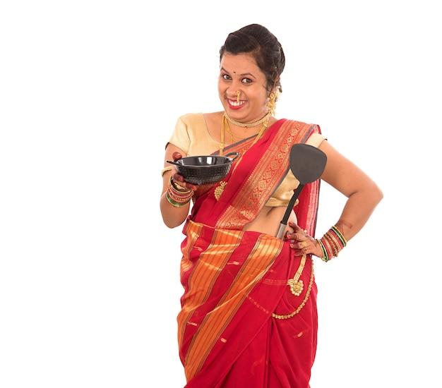 Giovane ragazza indiana tradizionale azienda utensile da cucina sul muro bianco