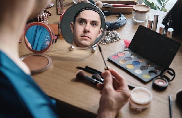 Giovane transgender che si guarda allo specchio mentre si applica il mascara sugli occhi