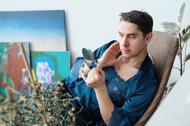 Giovane transgender seduto in poltrona e guardando lo specchio si applica una crema idratante sulla pelle
