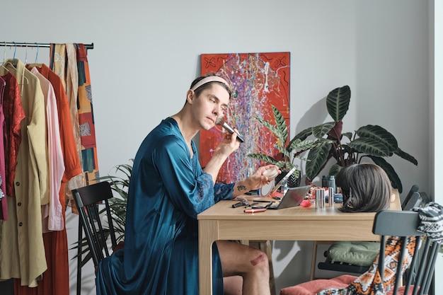 Giovane transessuale seduto al tavolo e truccato sul viso nel camerino