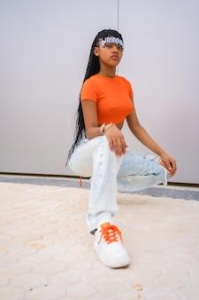 Una giovane ballerina trap con le trecce. ragazza etnica nera con t-shirt arancione e pantaloni da cowboy su sfondo grigio, in una posa da rapper urbano