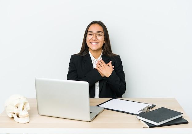 La giovane donna asiatica del traumatologo isolata sulla parete bianca ha un'espressione amichevole, premendo il palmo al petto. concetto di amore.