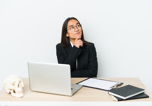 Giovane donna asiatica traumatologo isolata sul muro bianco che guarda lateralmente con espressione dubbiosa e scettica.
